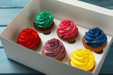 Box with different cupcakes on light blue wooden table, closeup
