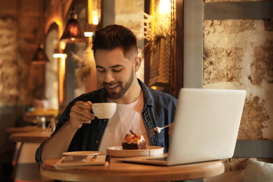 Young blogger with laptop eating dessert and drinking coffee at table in cafe