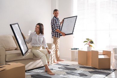 Happy couple decorating room with pictures together. Interior design