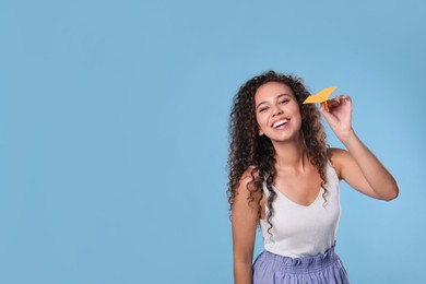 Beautiful African-American woman playing with paper plane on light blue background. Space for text