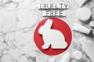 Flat lay of cards with phrase Cruelty Free, rabbit figure and personal care products on white marble table. Stop animal tests