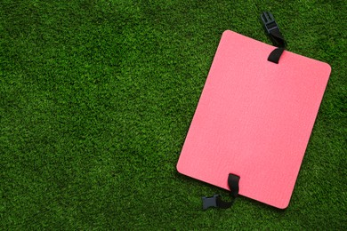 Pink foam tourist seat mat on green grass, top view. Space for text