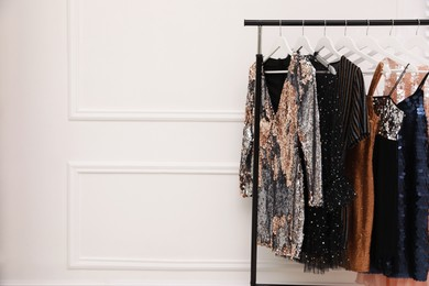 Collection of trendy women's garments on rack near white wall indoors, space for text. Clothing rental service