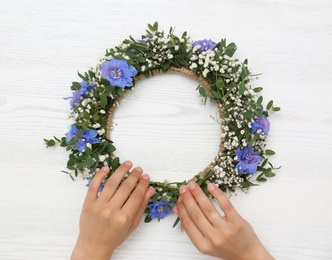 Woman making flower wreath at white wooden table, closeup