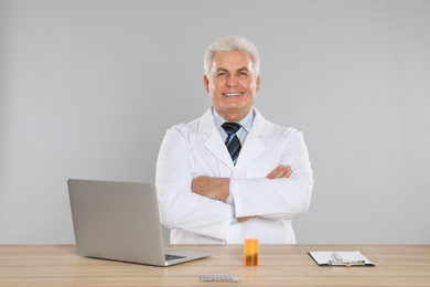 Professional pharmacist with laptop at table against light grey background