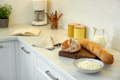 Fresh bread and dairy products on countertop in modern kitchen. Space for text