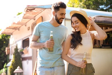 Happy couple with bottles of beer near motorhome. Camping season