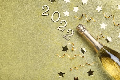 Bottle of sparkling wine, festive decor and number 2022 on golden background, flat lay with space for text. Happy New Year