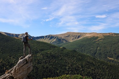 Man with trekking poles enjoying picturesque view on cliff in mountains. Space for text
