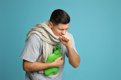 Ill man with hot water bottle and knitted scarf coughing on light blue background