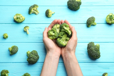 Woman holding fresh green broccoli on blue wooden table, top view