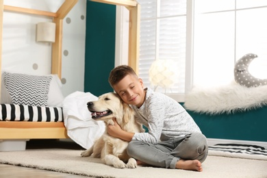 Little boy with his dog in stylish bedroom interior