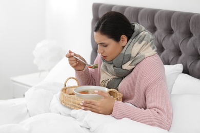 Sick young woman eating soup to cure flu in bed at home