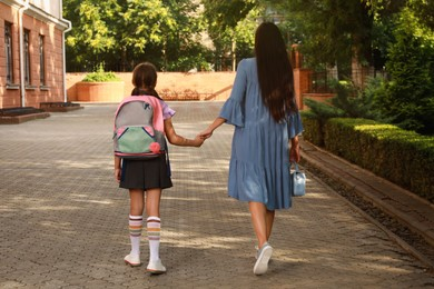 Mother taking her daughter to school, back view