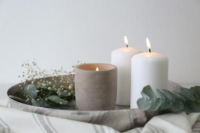 Beautiful eucalyptus branches, flowers and burning candles on fabric, closeup. Interior element