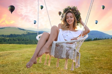 Dream world. Young woman swinging over green meadow near mountains, hot air balloons in sunset sky on background