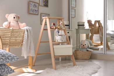 Decorative ladder with toys and different stuff in stylish baby room. Idea for interior design