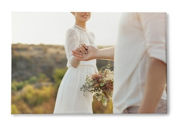 Photo printed on canvas, white background. Happy newlyweds with beautiful bouquet outdoors, closeup