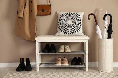 Stylish storage bench with different pairs of shoes near beige wall in hall