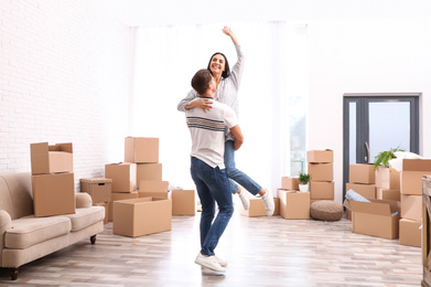 Happy couple having fun in room with cardboard boxes on moving day