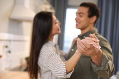 Lovely young interracial couple dancing at home, focus on hands