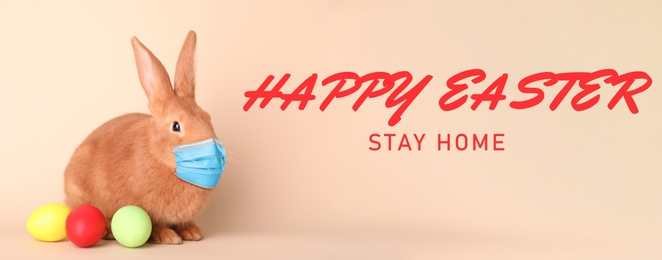Text Happy Easter Stay Home and cute bunny in protective mask on beige background, banner design. Holiday during Covid-19 pandemic