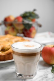 Glass of coffee and traditional apple pie on white marble table