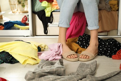 Young woman near wardrobe with different clothes indoors, closeup. Fast fashion concept