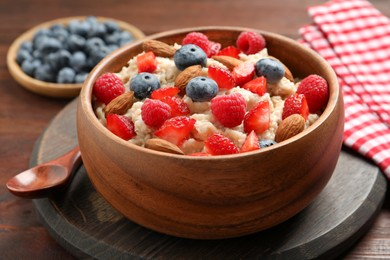 Tasty oatmeal porridge with berries and almond nuts in bowl served on wooden table