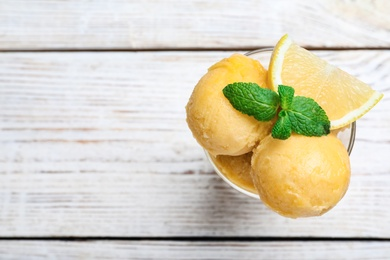 Yummy lemon ice cream in dessert bowl on wooden table, top view. Space for text