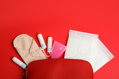 Tampons and other menstrual hygienic products on red background, flat lay