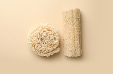 Natural shower loofah sponges on beige background, flat lay