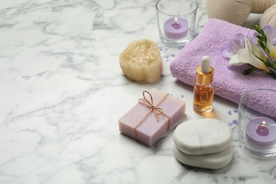Spa composition with skin care products on white marble table, space for text