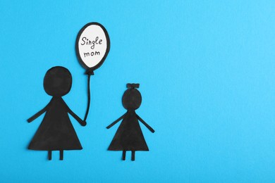 Being single mother concept. Woman with her child made of paper on light blue background, flat lay and space for text