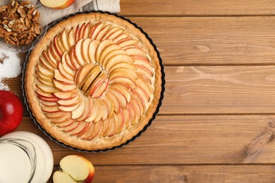 Delicious homemade apple tart and ingredients on wooden table, flat lay. Space for text