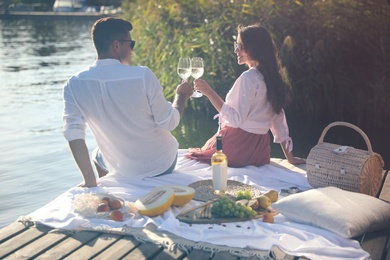 Couple clinking glasses with wine on pier at picnic, back view