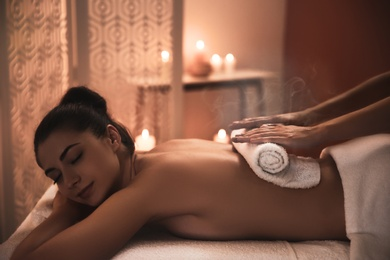 Young woman receiving hot towel massage in spa salon
