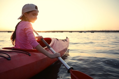 Happy girl kayaking on river at sunset. Summer camp activity