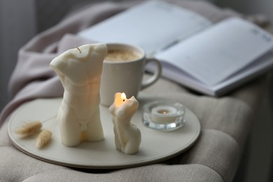 Beautiful body shaped candles and cup of hot drink on bench indoors