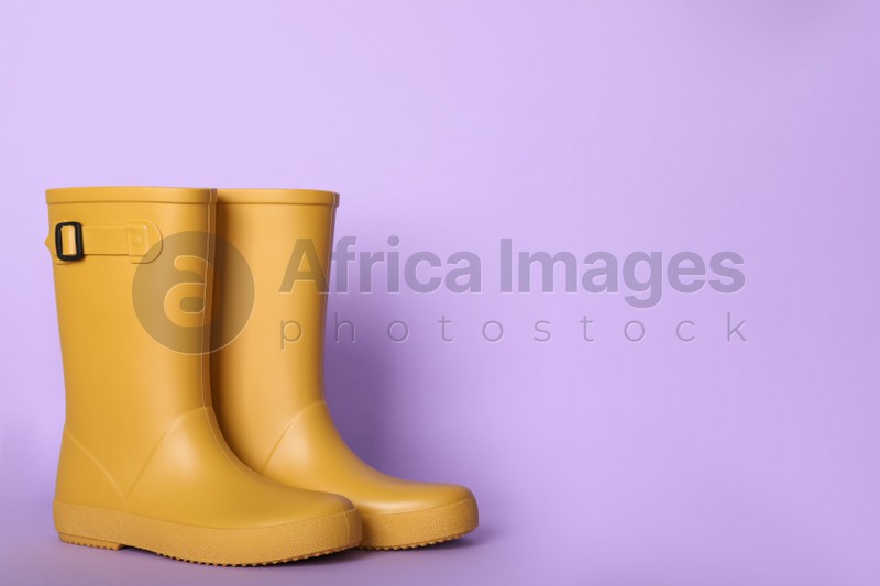 Yellow rubber boots on violet background. Space for text