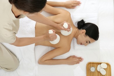 Young woman receiving herbal bag massage in spa salon, top view