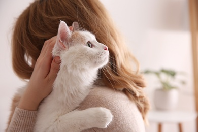 Woman with cute fluffy cat indoors, closeup