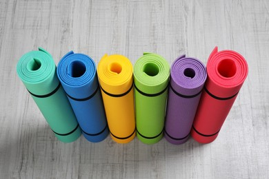 Bright rolled camping mats on white wooden background