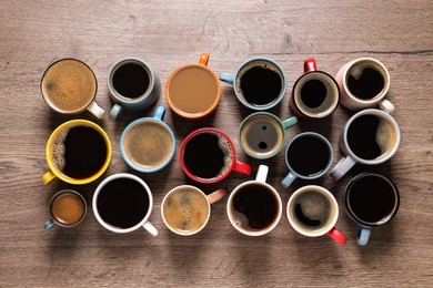 Cups of hot coffee on wooden table, flat lay