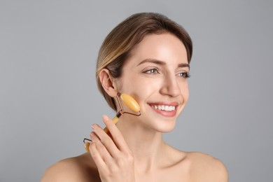 Young woman using natural jade face roller on light grey background
