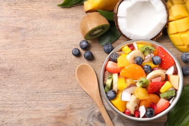 Delicious fresh fruit salad in bowl on wooden table, flat lay. Space for text