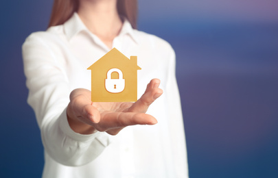 Home security concept. Woman holding house on color background, closeup