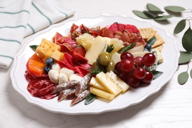 Tasty assorted appetizers served on white wooden table