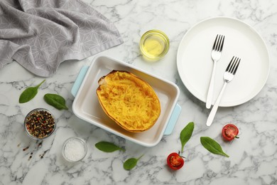 Half of cooked spaghetti squash in baking dish, plate and ingredients on white marble table, flat lay