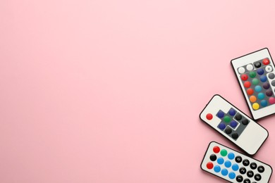 Different remote controls on pink background, flat lay. Space for text